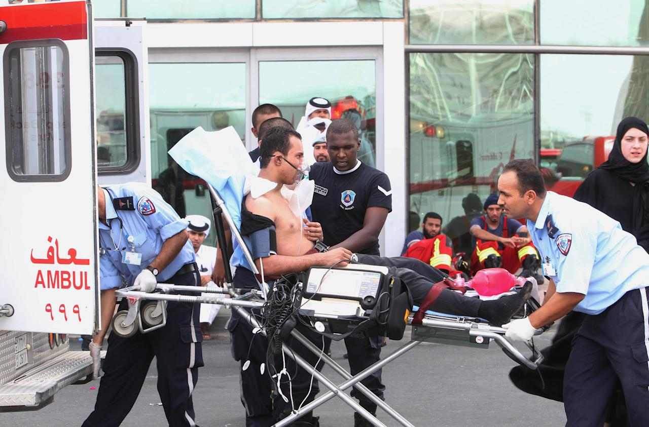 A survivor of a fire receives medical attention after a fire took hold of the Villaggio Mall, in Doha's west end, in the Qatari capital of Doha Monday May 28, 2012. Qatar's Interior Ministry said 13 children were among 19 people killed in a fire that broke out at one of the Gulf state's fanciest shopping mall on Monday. The Villaggio opened in 2006 and is one of Qatar's most popular shopping and amusement destinations. It includes an ice skating rink and indoor Venice-style gondola rides. (AP Photo/Osama Faisal)