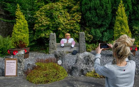 "The residents of ­Kettlewell have put Donald Trump in the stocks. Not the president himself but, perhaps fittingly, a straw-man version. He is one of 100 scarecrows on display around this pretty village in the Yorkshire Dales this past week. The Kettlewell Scarecrow Festival is said to be the biggest of its kind in the country – more than 15,000 people will have travelled from around the UK to ­admire the locals' handiwork – all 350 villagers work for months to ­ensure each year is a triumph.  Without the school, Kettlewell would become a village of retirement and holiday homesMaggie Walker The real success, though, is how it has changed the fortunes of ­Kettlewell. While many of Britain's rural communities face shrinking services and an exodus of the young, Kettlewell has bucked the trend. The village has three pubs, a post office, a shop, a school, a youth hostel and a very lively village hall. And it is the money raised from the annual scarecrow festival that has ensured their continued survival. Nicky Fairweather moved to the ­village four years ago because there was a school for her son Jake, seven, to attend (it will have 31 pupils this ­September). Outside their front door is a medieval crusader, which Nicky made at a workshop a few weeks ago in the ­village hall, bonding with other locals while stuffing hay into tights and coming up with wildly creative concepts – woolly mammoth, anyone?  Donald Trump in the stocks in the centre of Kettlewell Credit: Charlotte Graham ""Everyone has to come together to make it a success,"" says Nicky, 45. ""Financially, it's been very important because it's a fragile situation – if you lose the school, you lose families, while others won't want to move to the village.""  The first festival took place in 1994 after a villager attended a similar event in France. Now, around 400 drivers pay £3 for parking in a local field and roughly 50 coaches wind up the road for one mad August week.  Last year the festival raised £8,000 each for the school, the village hall and the church, leaving a few thousand for other community projects, such as the toddler group and cricket team.  A caveman and a woolly mammoth on the trail Credit: Charlotte Graham This year has two themed trails for visitors to follow; historical eras for the children, and rock and pop stars for the adults (straw likenesses of Freddie Mercury and Amy Winehouse being particularly fine examples). Outside the vicarage, the Rev James Theodosius, ­apparently a dab hand at the guitar himself, has created a Ziggy Stardust tableaux, complete with sound system.  One good thing is we don't have to have so many coffee mornings to keep things goingSue Nelson The residents of one road, off the main trail, have created a theme of their own, based on Charlie and the ­Chocolate Factory, while straw squirrels surround the post office and youth hostel. ""There's a lot of healthy competition,"" says Maggie Walker, a festival committee member. ""And a lot of pressure to make each year better than the last."" Although her own children flew the nest years ago, Maggie dreads the idea of public services ­disappearing through lack of funds. ""Without the school, Kettlewell would become a village of retirement and holiday homes,"" she says. ""I don't want to live in a retirement village. I like ­having friends Nicky's age.""  The residents' straw-powered community spirit has seen them weather plenty of challenges, such as when the council stopped their bus service 18 months ago. The solution? They started their own. Up at St Mary's Church, there is a straw baptism taking place, a straw wedding and even a straw funeral party. What the children love the most, though, is a straw skeleton escaping from a grave.  A straw funeral party at St Mary's  Credit: Charlotte Graham ""We've had a few inappropriate ones over the years,"" says Maggie, with a wicked twinkle. There was a phase when some villagers would put the scarecrows in naughty poses. In the village hall, the vicar's wife, Mo Theodosius, is working flat out with other villagers, serving tea, cakes, sandwiches and quiches to a snaking queue of festival-goers. Sue Nelson bakes dozens of cakes in the run-up to the week, commandeering freezers around the village. Each night she bakes 24 buns. ""It's hard work but the camaraderie is very good,"" says the 69-year-old. Children busily clear tables. The ­festival hasn't just ensured the financial future of the village, but brought generations together. A villager for 42 years, Sue remembers what Kettlewell was like before its festival fame.  ""One good thing is we don't have to have so many coffee mornings to keep things going. We couldn't afford it!"" she jokes. But, she adds seriously, ""if we want the village to thrive, we've got no choice but to be proactive and help ourselves.""  kettlewellscarecrowfestival.co.uk"