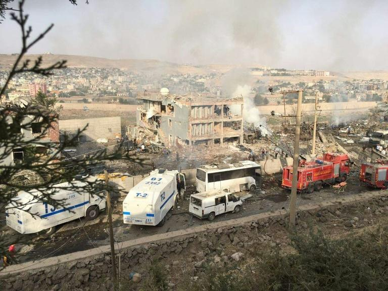 Turkish police and firefighters parked near a destroyed police headquarters in Cizre, southeastern Turkey, after a car bombing on August 26, 2016