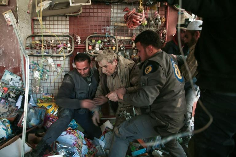 In this file photo taken on March 25, 2017, White Helmets volunteers rescue a survivor following reported air-strikes on the rebel-held town of Hammuriyeh