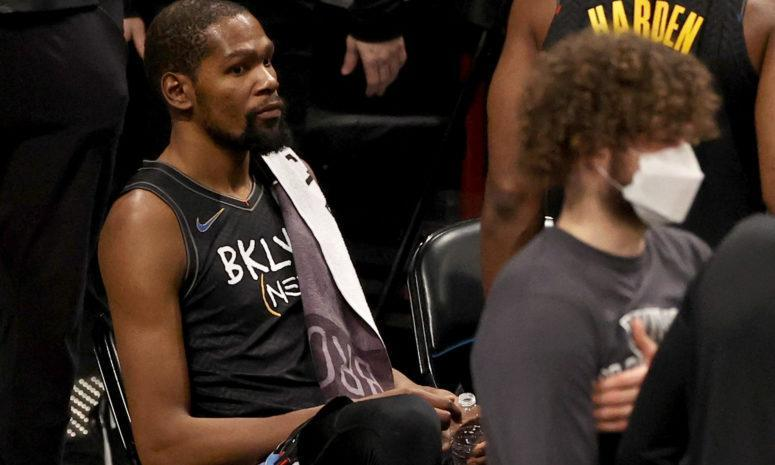 Kevin Durant sitting on the Nets' bench.