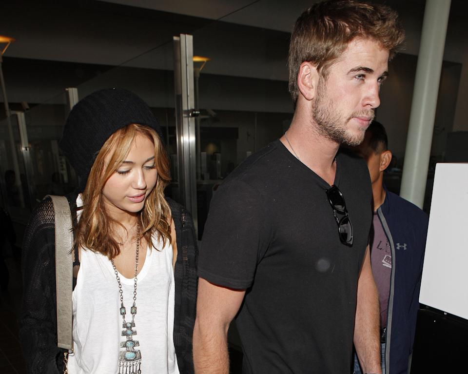 Miley Cyrus and Liam Hemsworth arrive at LAX airport on June 21, 2010 in Los Angeles, California. (Photo by Jean Baptiste Lacroix/WireImage)