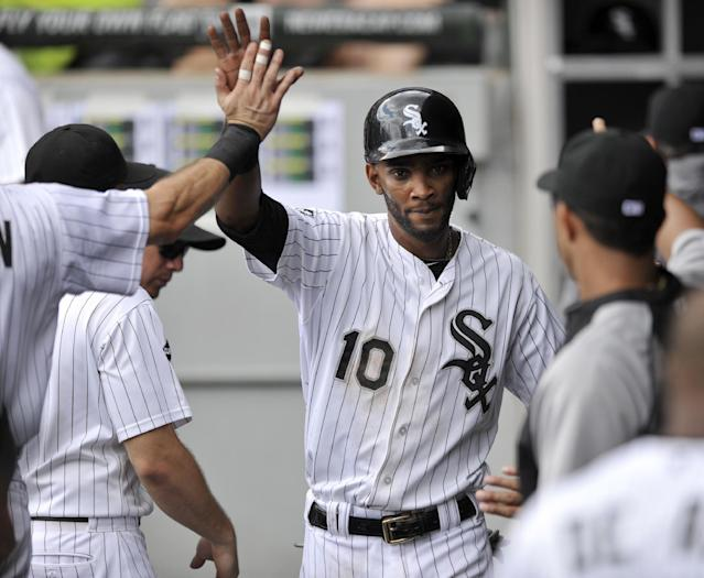 Chicago White Sox's Alexei Ramirez (10) celebrates with teammates in the dugout after scoring on an error committed by Detroit Tigers second baseman Ian Kinsler during the first inning of the first game of a baseball doubleheader in Chicago, Saturday, Aug. 30, 2014. (AP Photo/Paul Beaty)