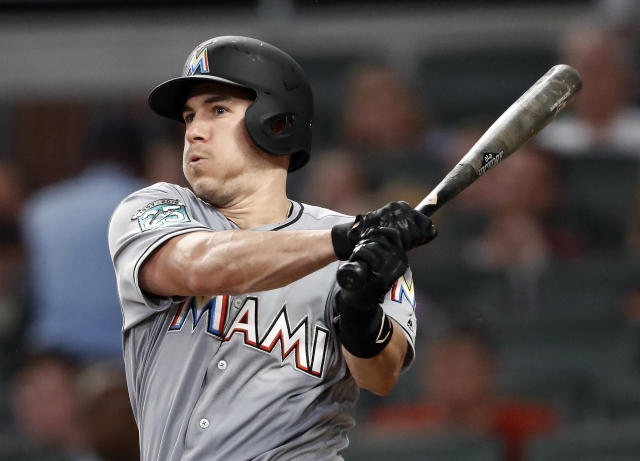 FILE - In this Tuesday, Aug. 14, 2018 file photo, Miami Marlins' J.T. Realmuto follows through on two-run base hit in the fourth inning of a baseball game against the Atlanta Braves in Atlanta. A person familiar with the negotiations says Miami Marlins All-Star catcher J.T. Realmuto has been traded to the Philadelphia Phillies for catcher Jorge Alfaro, two pitching prospects and international bonus pool allocation. The person confirmed the trade to The Associated Press on condition of anonymity Thursday, Feb. 7, 2019 because the teams had not announced it. (AP Photo/John Bazemore, File)