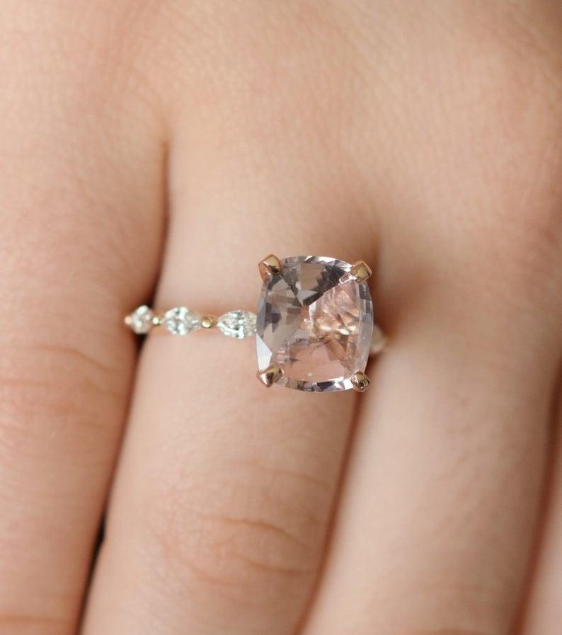 """<p>The sapphire in the <a href=""""https://www.popsugar.com/buy/Peach-Sapphire-Rose-Gold-Engagement-Ring-531241?p_name=Peach%20Sapphire%20Rose%20Gold%20Engagement%20Ring&retailer=etsy.com&pid=531241&price=4%2C500&evar1=fab%3Aus&evar9=44555978&evar98=https%3A%2F%2Fwww.popsugar.com%2Fphoto-gallery%2F44555978%2Fimage%2F47011790%2FPeach-Sapphire-Rose-Gold-Engagement-Ring&list1=wedding%2Cjewelry%2Crose%20gold%2Cengagement%20rings&prop13=api&pdata=1"""" rel=""""nofollow noopener"""" class=""""link rapid-noclick-resp"""" target=""""_blank"""" data-ylk=""""slk:Peach Sapphire Rose Gold Engagement Ring"""">Peach Sapphire Rose Gold Engagement Ring</a> ($4,500) changes color from ginger to peach depending on the lighting. </p>"""