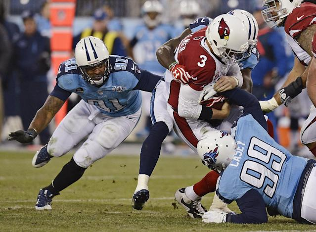 Arizona Cardinals quarterback Carson Palmer (3) is sacked for a 7-yard loss by Tennessee Titans defensive tackle Jurrell Casey (99) and Derrick Morgan (91) in the second quarter of an NFL football game Sunday, Dec. 15, 2013, in Nashville, Tenn. (AP Photo/Mark Zaleski)