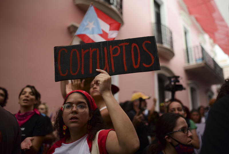 "A young woman holds a sign that reads in Spanish ""Corrupt"" while protesting outside the executive mansion known as La Fortaleza, in Old San Juan, demanding the resignation of Governor Wanda Vazquez after the discovery of an old warehouse filled with unused emergency supplies in San Juan, Puerto Rico, Monday, Jan. 20, 2020. Anger erupted on Saturday after an online blogger posted a live video of the warehouse in the southern coastal city of Ponce filled with water bottles, cots, baby food and other basic supplies that had apparently been sitting there since Hurricane Maria battered the U.S. territory in September 2017. (AP Photo/Carlos Giusti)"
