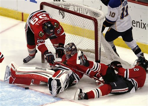 As Chicago Blackhawks goalie Corey Crawford stops a St. Louis Blues shot, teammates Bryan Bickell, left, and Duncan Keith, right, crash into him and the net during the third period of an NHL game Sunday, Feb. 19, 2012, in Chicago. Chicago won 3-1. (AP Photo/John Smierciak)