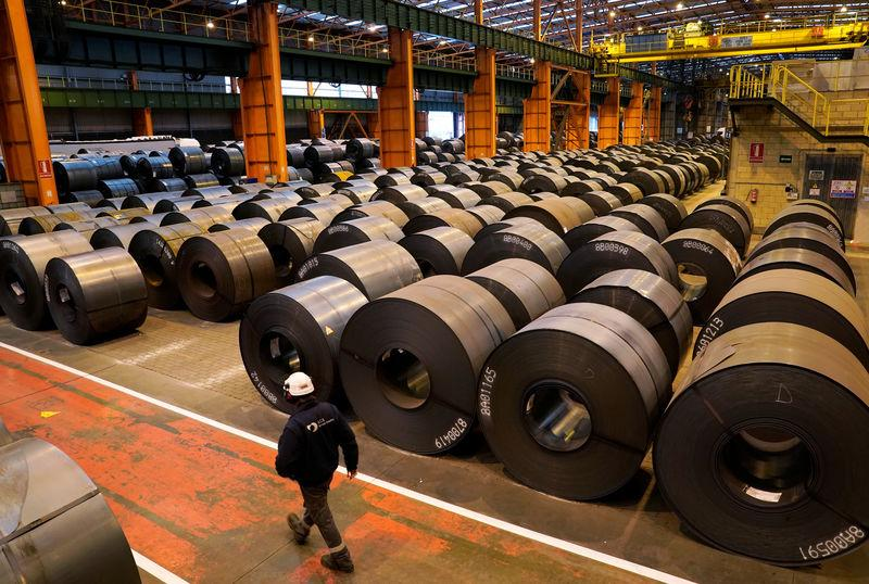 A worker walks past steel rolls at the ArcelorMittal steel plant in Sestao