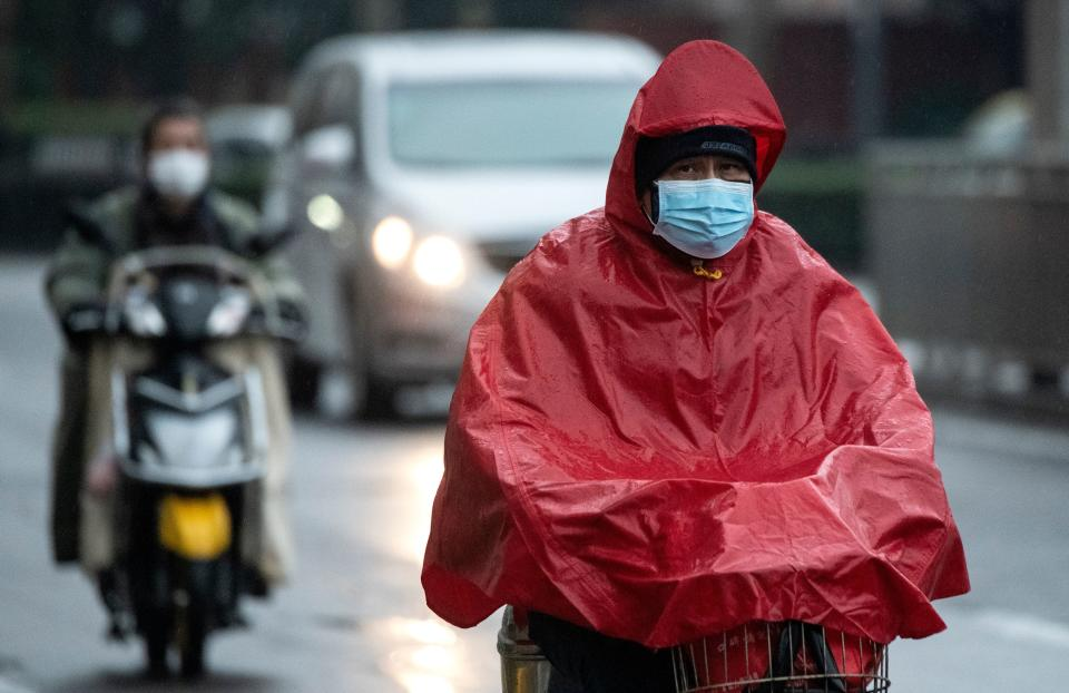 """A man wearing a protective face mask commutes on a road as it rains in Shanghai on February 11, 2020. - The death toll from a new coronavirus outbreak surged past 1,000 on February 11 as the World Health Organization warned infected people who have not travelled to China could be the spark for a """"bigger fire"""". (Photo by NOEL CELIS / AFP) (Photo by NOEL CELIS/AFP via Getty Images)"""