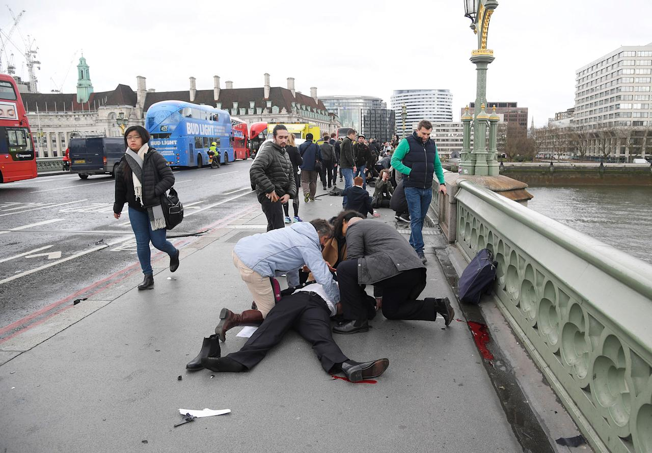 <p>People assited several injured victims on Westminster Bridge after a car mowed over many in London on 22 March 2017. [Toby Melville | Reuters] </p>