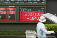 A woman rides a bicycle past screens showing Japan's Nikkei 225 index at a securities firm in Tokyo on Friday, Sept. 25, 2020. Asian shares advanced Friday, cheered by a modest rally on Wall Street and rising hopes for fresh stimulus for the U.S. economy.(AP Photo/Hiro Komae)