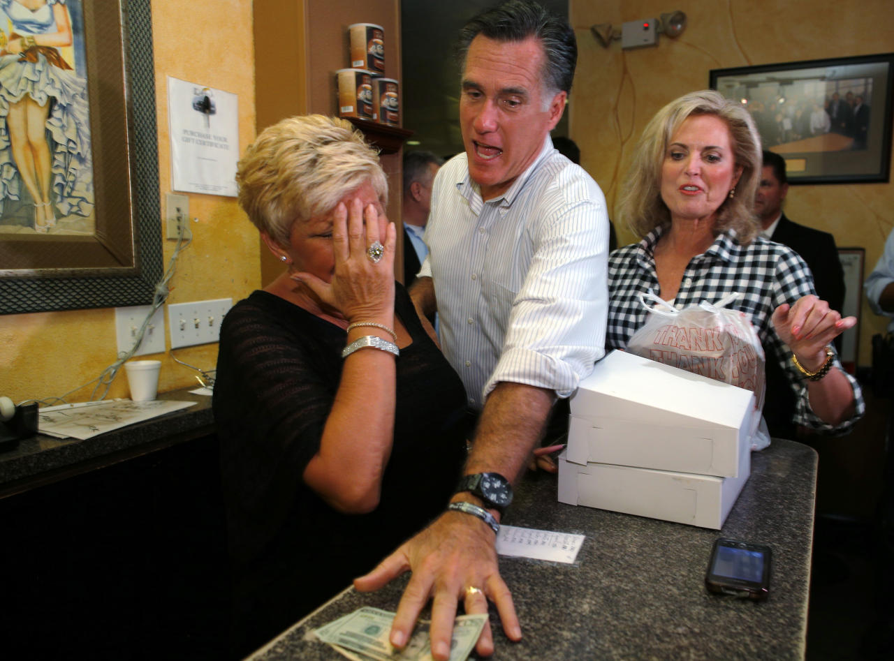 Republican presidential nominee Mitt Romney, with his wife Ann at his side, insists on paying for pastries and soup during a visit to La Tersesita Restaurant in Tampa, Florida October 5, 2012.   REUTERS/Brian Snyder (UNITED STATES - Tags: POLITICS ELECTIONS USA PRESIDENTIAL ELECTION TPX IMAGES OF THE DAY)