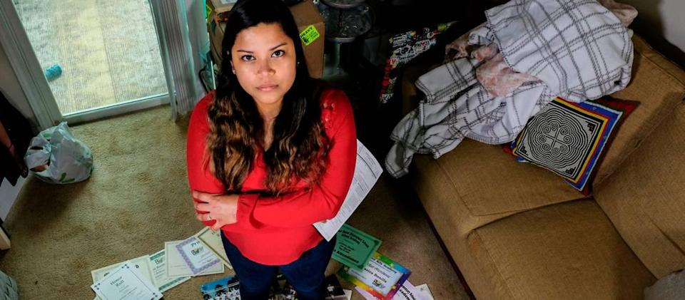 Jessica Bonilla Garcia, 27, stands for a portrait on April 15, 2021 in her apartment in Ridgeland, S.C. with her DACA renewal paperwork in hand. Nine years ago, Garcia used the photos and rewards surrounding her, collected from her life in South Carolina since she was 4, to apply for DACA for the first time. She fills out new forms and pays $495 to renew her status every 21 months.