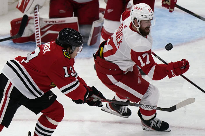 Detroit Red Wings defenseman Filip Hronek, right, controls the puck next to Chicago Blackhawks center Mattias Janmark during the third period of an NHL hockey game in Chicago, Saturday, Feb. 27, 2021. (AP Photo/Nam Y. Huh)
