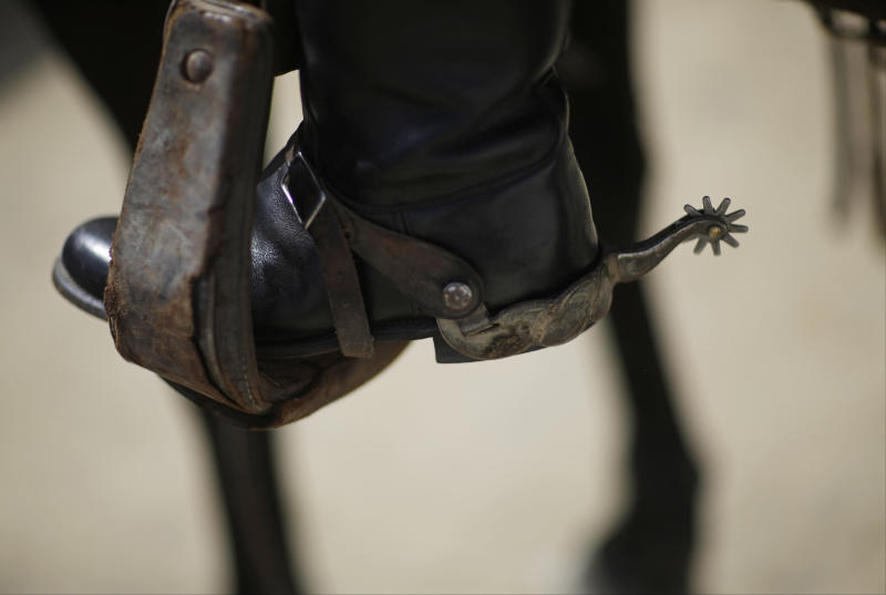 The heel of an outrider is seen following a race before the 140th running of the Kentucky Derby horse race at Churchill Downs Saturday, May 3, 2014, in Louisville, Ky. (AP Photo/David Goldman)