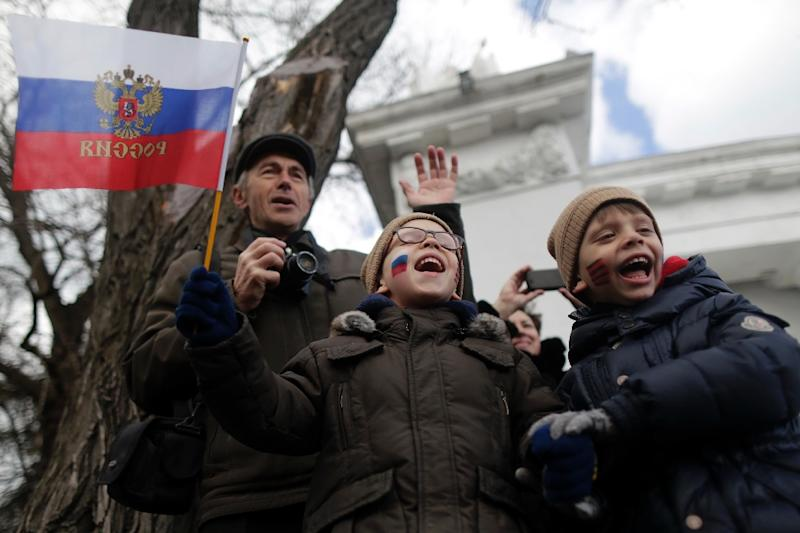 Boys shout slogans during celebrations in Sevastopol on March 18, 2015, to mark one year since Russia's President Vladimir Putin signed off on the annexation of Crimea