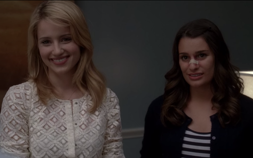 Quinn Fabray, wearing a white lace sweater, smiles brightly while Rachel Berry grimaces as her nose is broken