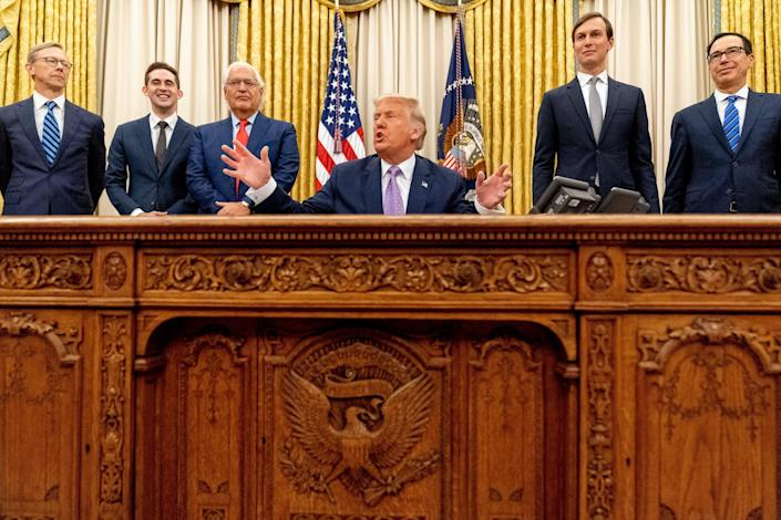 President Donald Trump, accompanied by from left, U.S. special envoy for Iran Brian Hook, Avraham Berkowitz, Assistant to the President and Special Representative for International Negotiations, U.S. Ambassador to Israel David Friedman, President Donald Trump's White House senior adviser Jared Kushner, and Treasury Secretary Steven Mnuchin, speaks in the Oval Office at the White House, Wednesday, Aug. 12, 2020, in Washington. Trump said on Thursday that the United Arab Emirates and Israel have agreed to establish full diplomatic ties as part of a deal to halt the annexation of occupied land sought by the Palestinians for their future state.