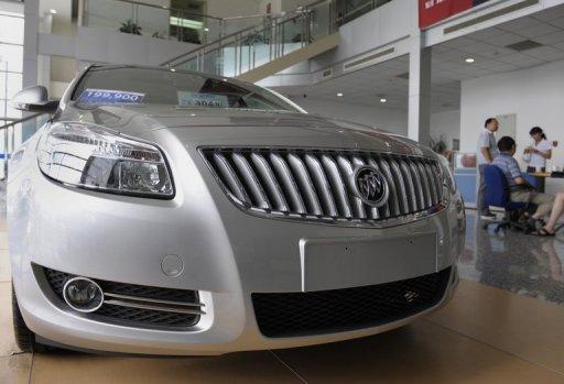 "Customers stand next to a new Buick sedan displayed at a General Motors dealership in Beijing 2009. China said Thursday it will ""withdraw support"" for foreign investment in auto manufacturing to encourage domestic industry in the world's largest car market"