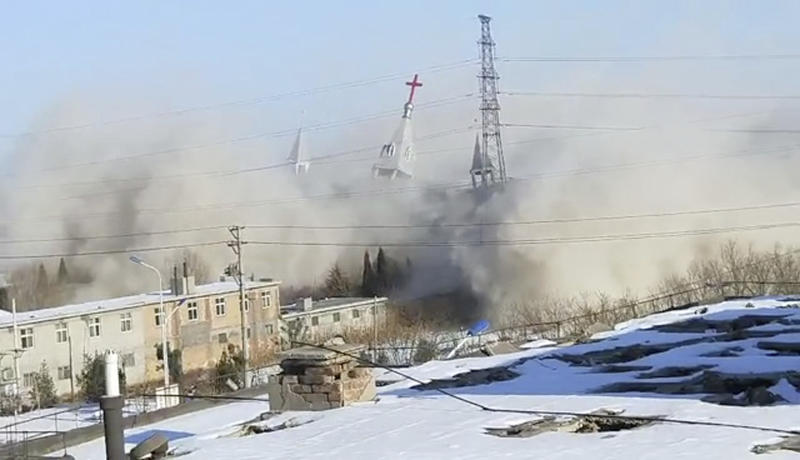 In this image taken from video shot Tuesday, Jan. 9, 2018, by China Aid and provided to the Associated Press, clouds of debris billow during the demolition of the Golden Lampstand Church in Linfen in northern China's Shanxi province. Witnesses and overseas activists say paramilitary troops known as the People's Armed Police used excavators and dynamite on Tuesday to destroy the Golden Lampstand Church, a Christian mega-church that clashed with the government. (China Aid via AP)