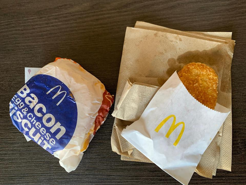 Mcdonald's packaged breakfast sandwich and hash browns on wooden table