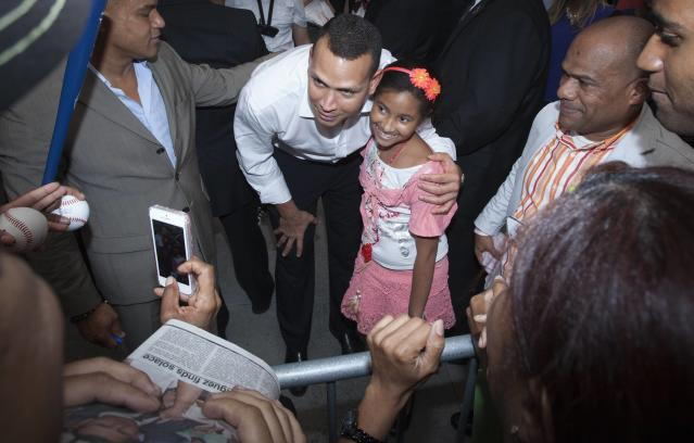 New York Yankees baseball player Alex Rodriguez poses for a photo with a supporter's child after leaving Major League Baseball's headquarters in New York