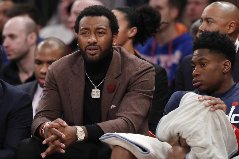 Injured Washington Wizards point guard John Wall, left, reacts as he watches the first half of an NBA basketball game against the New York Knicks in New York, Monday, Dec. 23, 2019. (AP Photo/Kathy Willens)