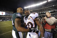 FILE - Philadelphia Eagles defensive end Juqua Parker (75) and Denver Broncos safety Brian Dawkins (20) meet on the field at the end of an NFL football game in Philadelphia, in this Sunday, Dec. 27, 2009, file photo. Dawkins, the seven-time Pro Bowl safety in 13 seasons in Philadelphia, returned as a Bronco in 2009. He hugged former teammates after the game and blew kisses to the fans as he ran off the field following a 30-27 loss. (AP Photo/Michael Perez, File)