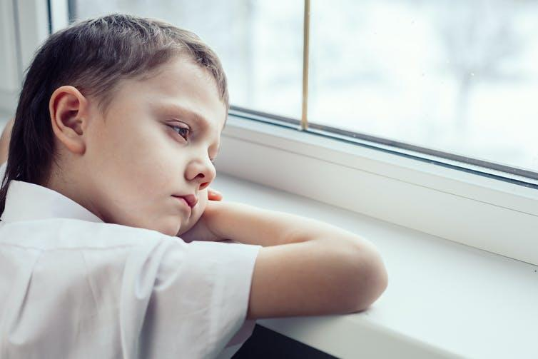 A tired child looking out the window