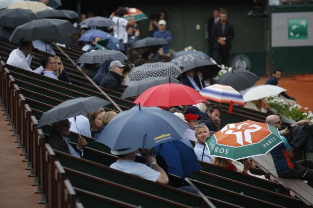 Spectators shield themselves from the rain during third round matches of the French Open tennis tournament at the Roland Garros stadium in Paris, France, Friday, June 1, 2018. (AP Photo/Michel Euler)