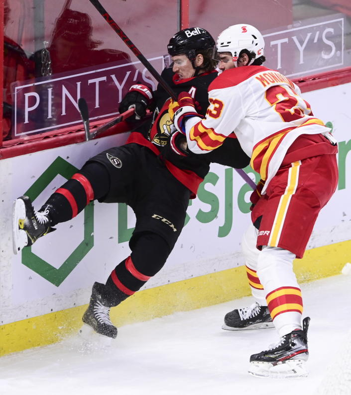 Calgary Flames centre Sean Monahan (23) puts Ottawa Senators defenseman Thomas Chabot (72) into the boards during third period NHL hockey action in Ottawa on Monday, March 1, 2021. (Sean Kilpatrick/The Canadian Press via AP)