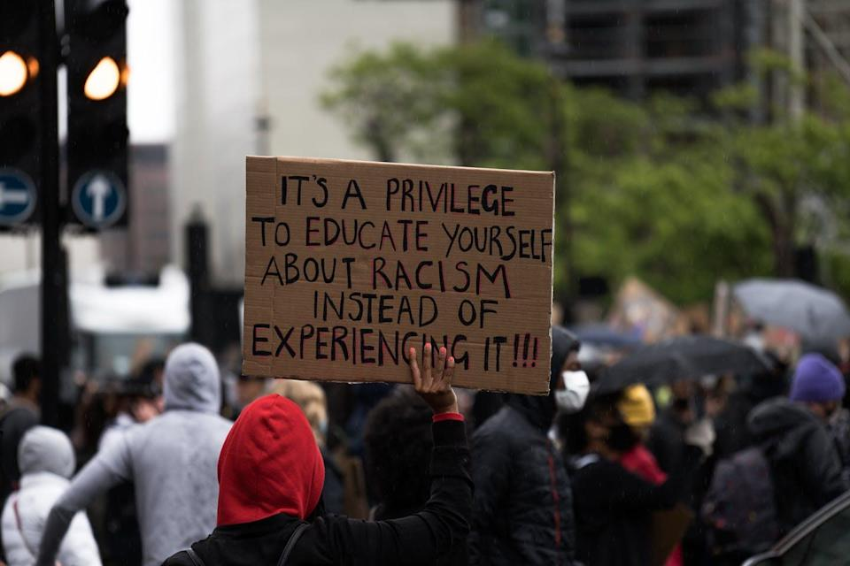A sign at a demonstration reads 'It's a privilege to educate yourself about racism instead of experiencing it.