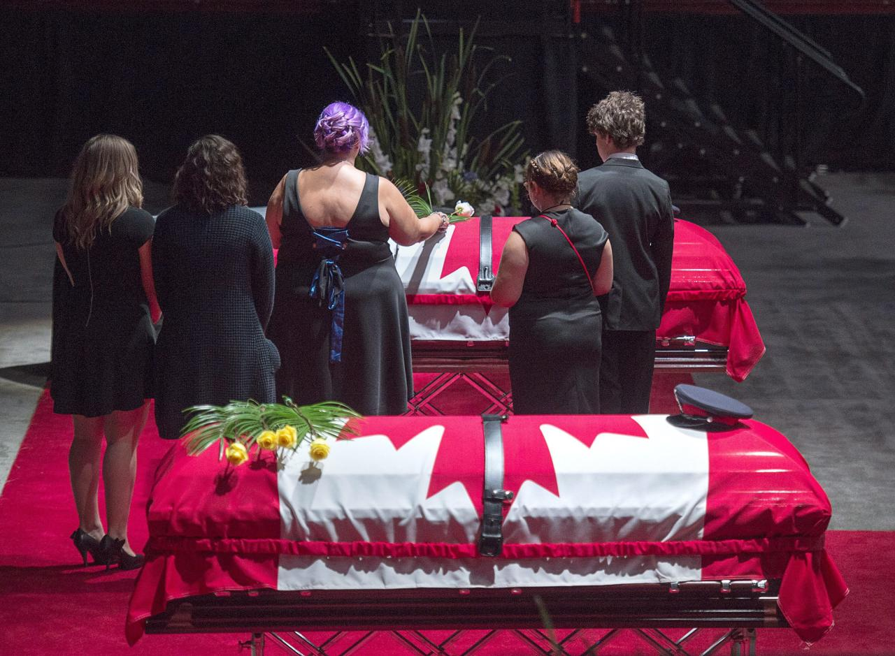 <p>Jackie McLean, accompanied by their children, places a rose on the casket for her husband, Const. Robb Costello, at the regimental funeral for Costello and Const. Sara Burns, killed in the line of duty, in Fredericton on Saturday, Aug. 18, 2018. The two city police officers were among four people who died in a shooting in a residential area on the city's north side. (Photo from The Canadian Press/Andrew Vaughan) </p>