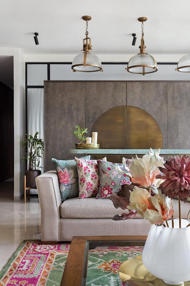 "A stone and brass bar unit serves as a minimalist backdrop that anchors the expansive living cum dining room. Bass echoes in the detailing of the pendant lamps, the legs of the bar table and the centerpiece on the coffee table. Pendant lamp by <a href=""https://fave.co/2QvqrQb"">Gulmohar Lane</a>; sofa by <a href=""https://fave.co/2qg4zh0"">Cottons and Satins</a>; throw cushions by <a href=""https://fave.co/37jLJG8"">Good Earth</a>; carpet by <a href=""https://fave.co/2Om0UpK"">Humming Haus</a>."