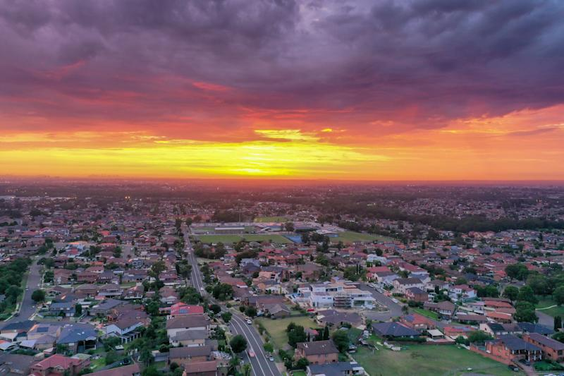 A sun rises above residential suburbs in Australia.