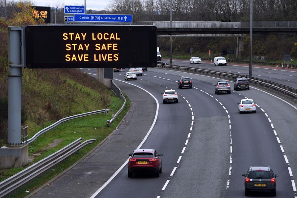 Cars pass a Covid warning sign on the eastbound M8 motorway in Glasgow ahead of the introduction of further coronavirus restrictions on November 20, 2020. - Swathes of western and central Scotland prepared to enter a three-week period of restrictions this evening. From 6:00 pm (1800 GMT) non-essential shops, hospitality, gyms and beauty salons will shut in 11 council areas including the most populous city of Glasgow. (Photo by Andy Buchanan / AFP) (Photo by ANDY BUCHANAN/AFP via Getty Images)