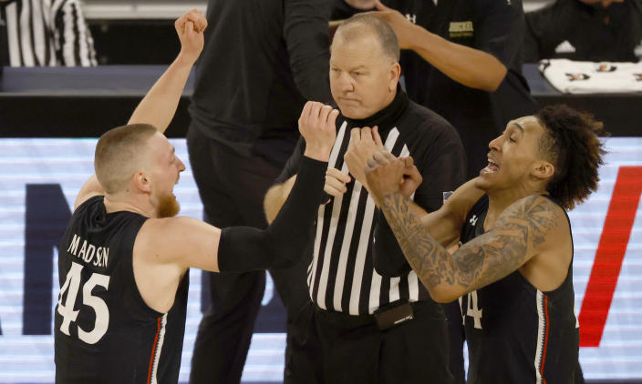 Cincinnati's Mason Madsen (45) and Jeremiah Davenport (24) celebrate following Cincinnati's win over Wichita State after an NCAA college basketball game in the semifinal round of the American Athletic Conference men's tournament Saturday, March 13, 2021, in Fort Worth, Texas. (AP Photo/Ron Jenkins)