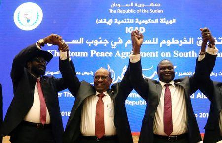 FILE PHOTO: South Sudan President Salva Kiir (L), Sudan's President Omar Al-Bashir (C) and South Sudan rebel leader Riek Machar hold hands after signing a peace agreement aimed to end a war in which tens of thousands of people have been killed, in Khartoum, Sudan June 27, 2018. REUTERS/Mohamed Nureldin Abdallah/File Photo