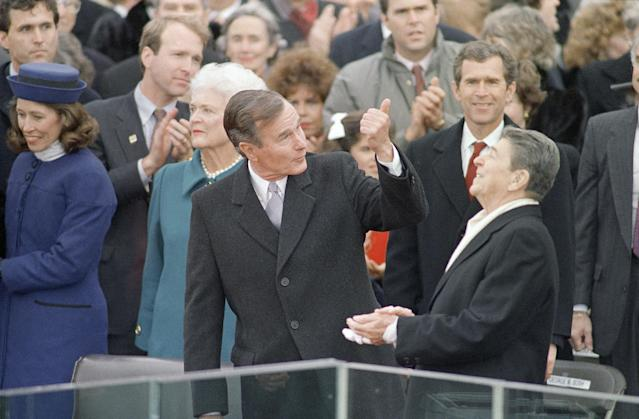 President-elect George Bush gives President Ronald Reagan a thumbs up as Reagan reacts prior to Bush being sworn in as the 41st president of the United States outside the Capitol, Jan. 20, 1989, in Washington. Behind Reagan is Bush's son George W. Bush. (AP Photo/Ron Edmonds)