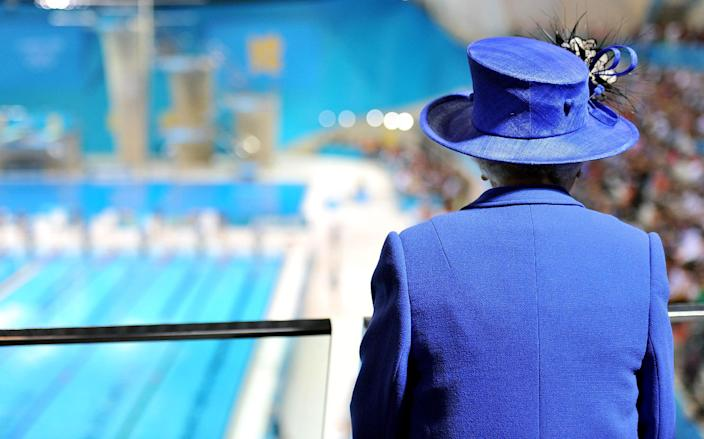 RETRANSMISSION TO REMOVE RESTRICTIONS - Queen Elizabeth II watches the morning session of swimming competitions at the Aquatics Centre in London during the 2012 Summer Olympics on Saturday, July 28, 2012. (AP Photo/Martin Rickett, Pool)