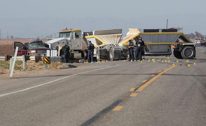 Investigators work the scene of a two vehicle crash that killed at least 13 people on Highway 115 near Holtville, Ca., March 2, 2021.