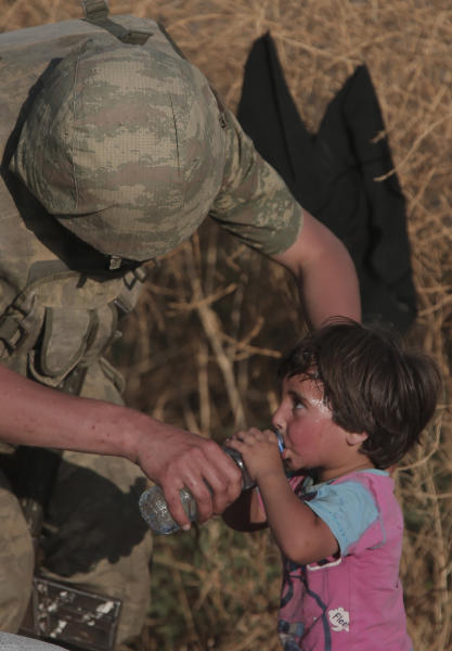File-This June 14, 2015, file photo shows a Turkish soldier offering water to a Syrian refugee child after crossing into Turkey from Syria, in Akcakale, Sanliurfa province, southeastern Turkey. The photo was taken in Turkey in 2015 by Associated Press photographer Lefteris Pitarakis, not during the recent offensive. The photo was widely shared on Twitter this week, suggesting that the recent assault in northern Syria has not hurt civilians.  (AP Photo/Lefteris Pitarakis, File)