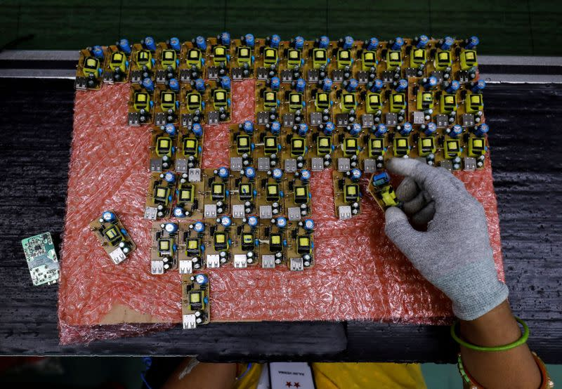 FILE PHOTO: A worker arranges battery charger circuit boards at a mobile phone battery manufacturing plant in Noida