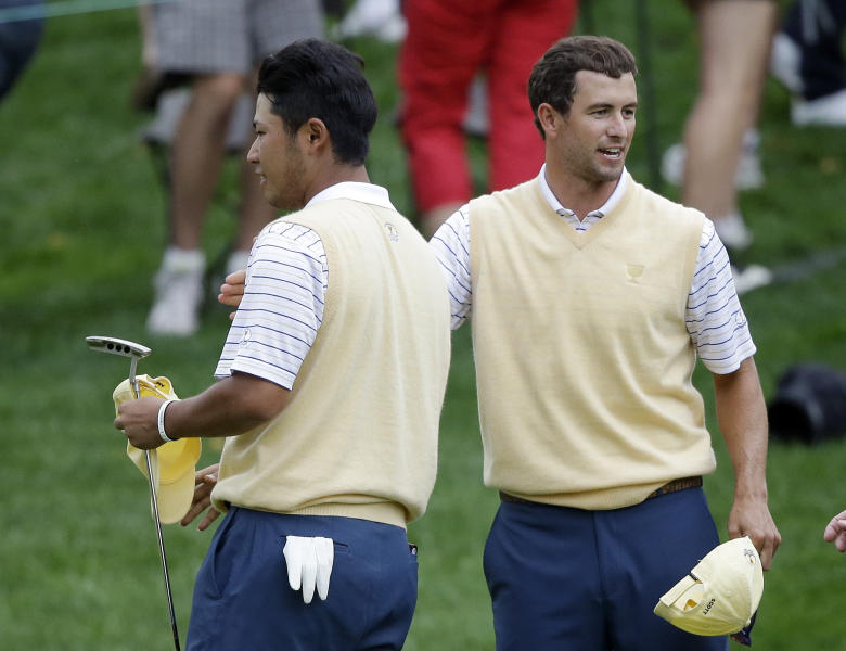 International team player Hideki Matsuyama, left, of Japan, and Adam Scott, of Australia, celebrate after defeating United States team player Zach Johnson and Jason Dufner in the foursome match at the Presidents Cup golf tournament at Muirfield Village Golf Club Saturday, Oct. 5, 2013, in Dublin, Ohio. (AP Photo/Darron Cummings)