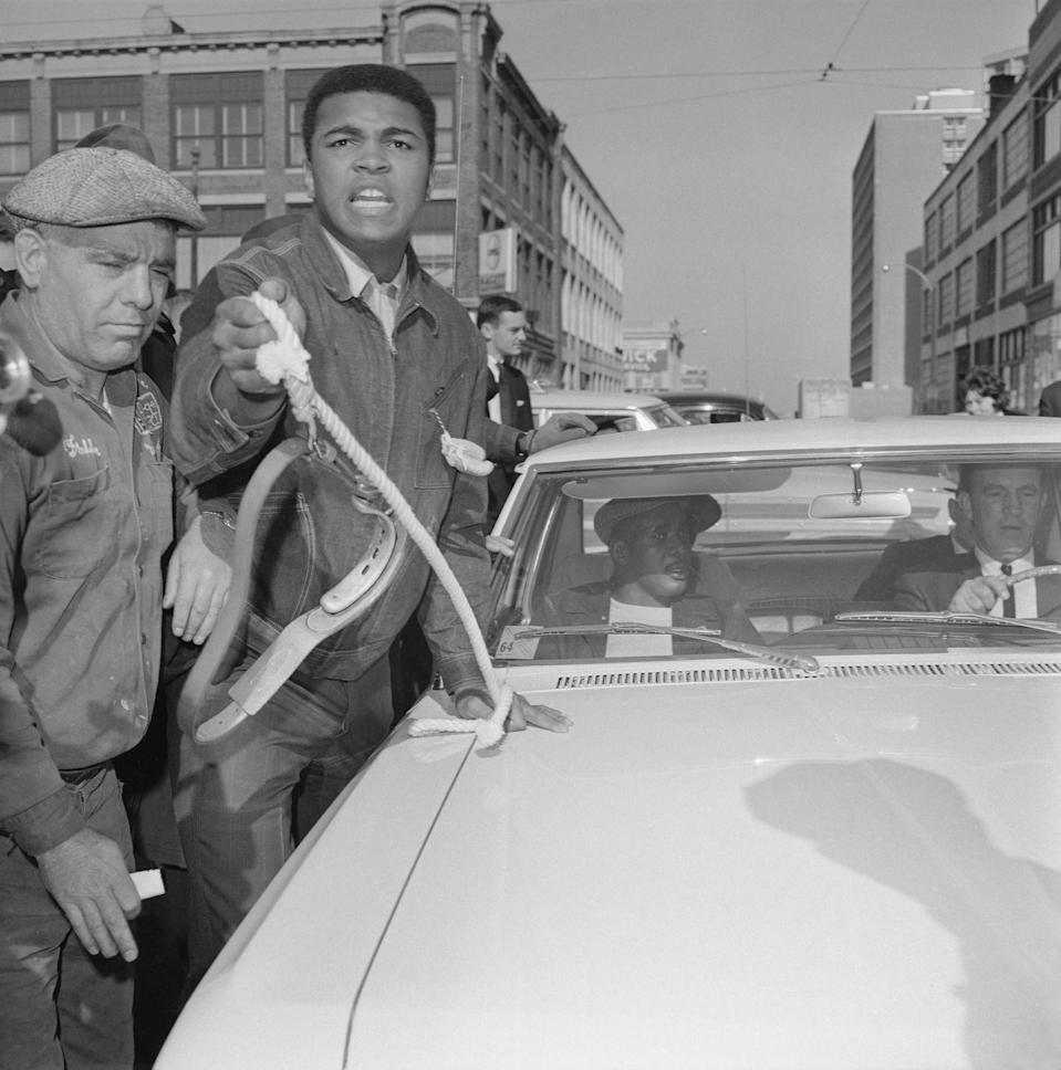 <p>Cassius Clay taunts Sonny Liston who sits in the car unperturbed as heavyweight champion Clay runs alongside the moving car, shouting. The challenger Sonny Liston was on his way to the boxing commission for a pre-fight physical checkup as was Clay. Both will meet in a title bout at Boston Garden.</p>