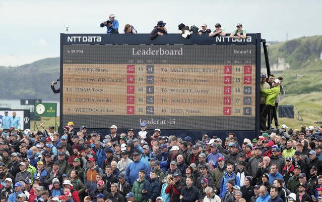 Spectators clamber on to and on top of a scoreboard as they vie to get a glimpse of Ireland's Shane Lowry and England's Tommy Fleetwood as they play during the final round of the British Open Golf Championships at Royal Portrush in Northern Ireland, Sunday, July 21, 2019. (AP Photo/Peter Morrison)