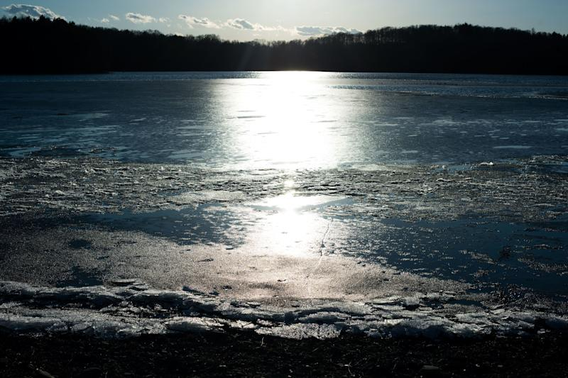 The sun shines across the water of the Lake Washington reservoir in Newburgh, New York.
