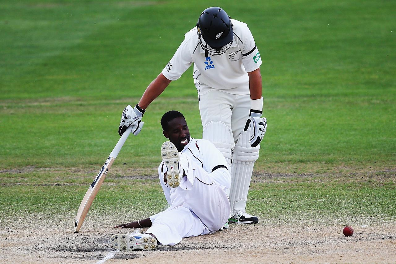 DUNEDIN, NEW ZEALAND - DECEMBER 07:  Shane Shillingford of the West Indies fields off his own bowling in front of Ross Taylor of New Zealand during day five of the first test match between New Zealand and the West Indies at University Oval on December 7, 2013 in Dunedin, New Zealand.  (Photo by Hannah Johnston/Getty Images)
