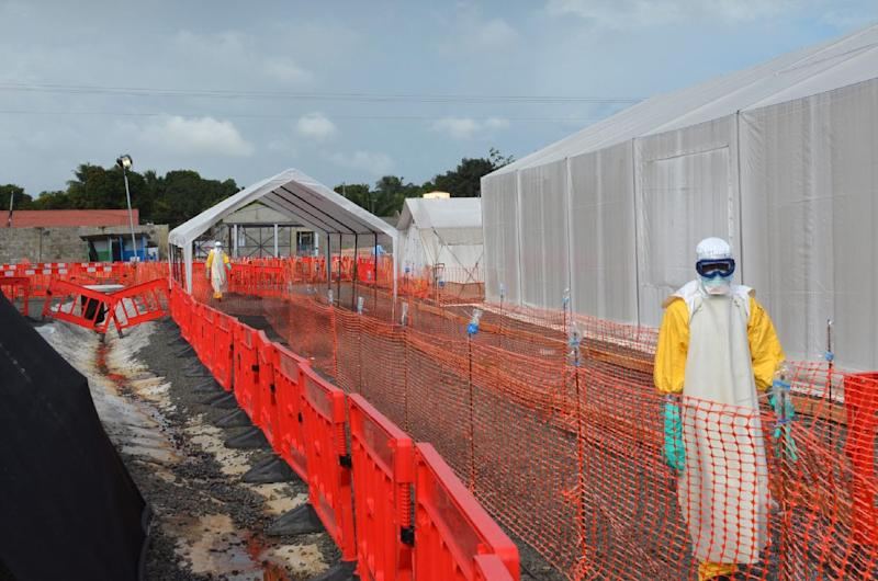 Health workers in protective gear stand outside an Ebola treatment centre in Monrovia (AFP Photo/Zoom Dosso)